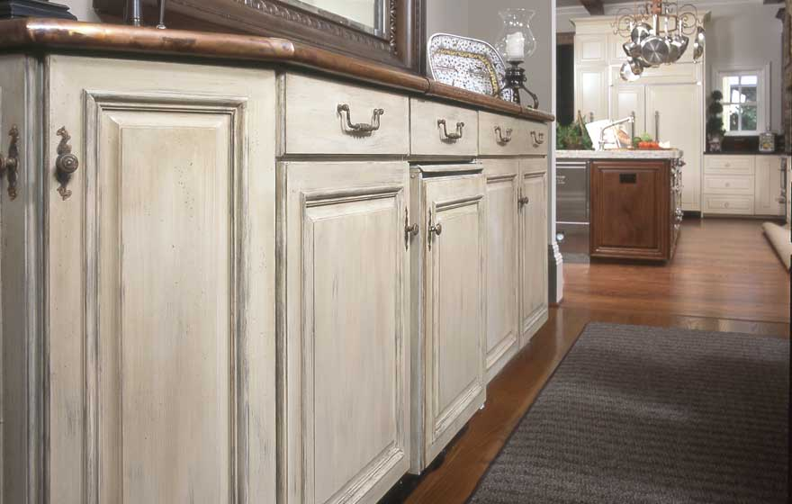 Using a unique paint and glaze application is an excellent option for a dining area hutch leading into a beautiful high end kitchen.
