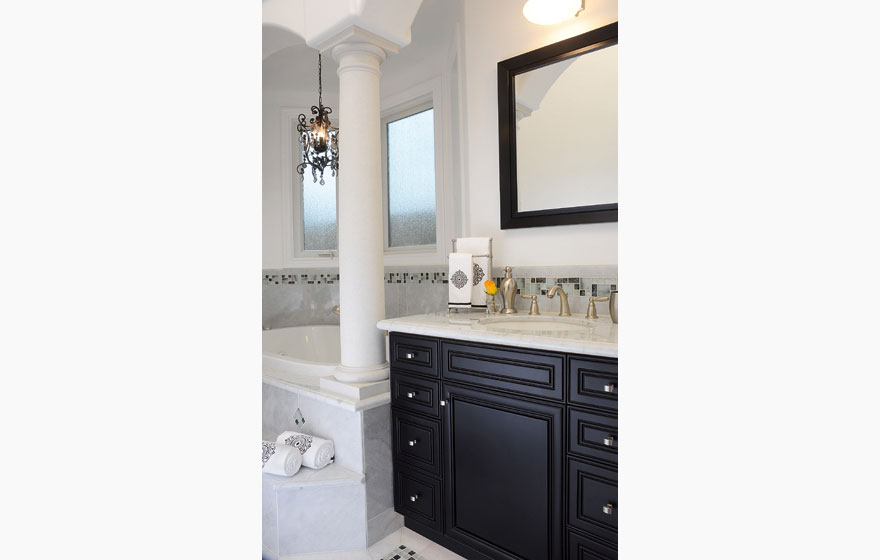 The contrast of dark cabinetry with light colored marble makes a dramatic statement.