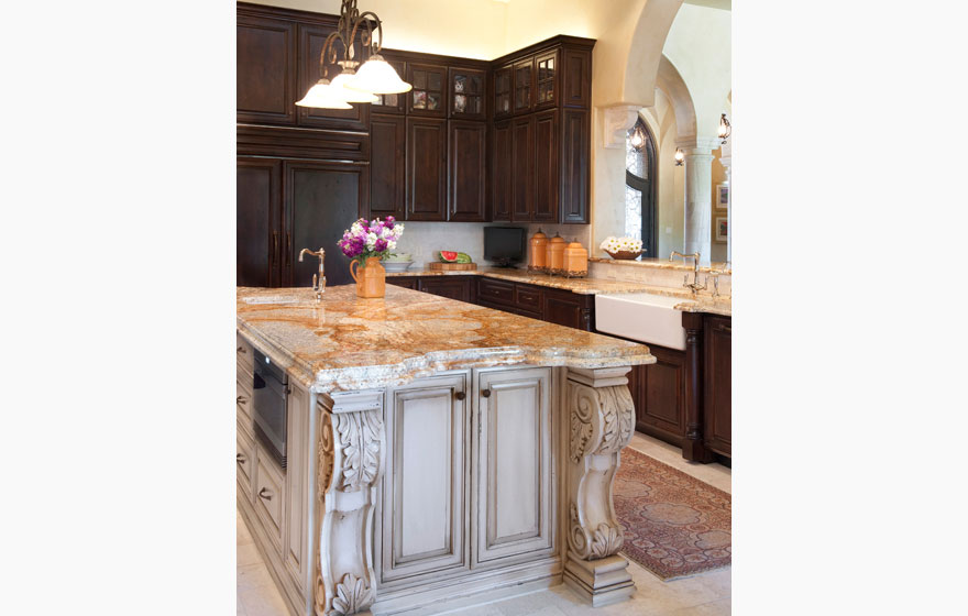 The stately rock work and ornate posts on the island command attention and are balanced by the delicate arched french lites in the hutch.