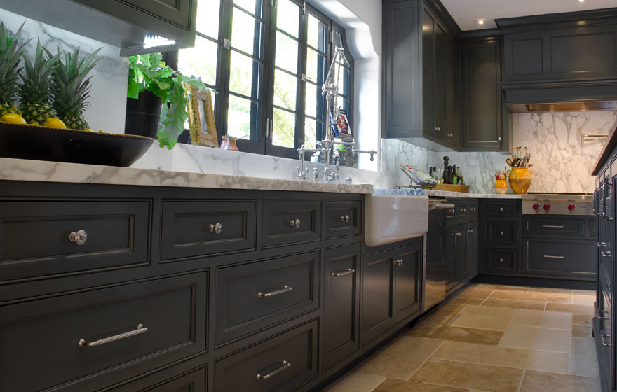 Dark paint creates a dramatic look in this kitchen with all the right custom details.