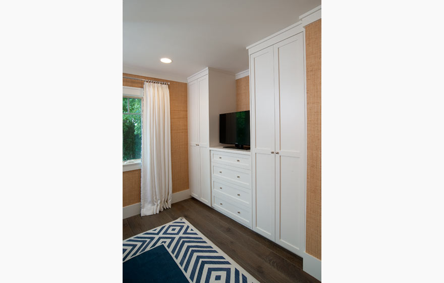 Built-in closet cabinets in this guest room provide ample space for hanging clothes and storage while maintaining a simple, clean appearance.