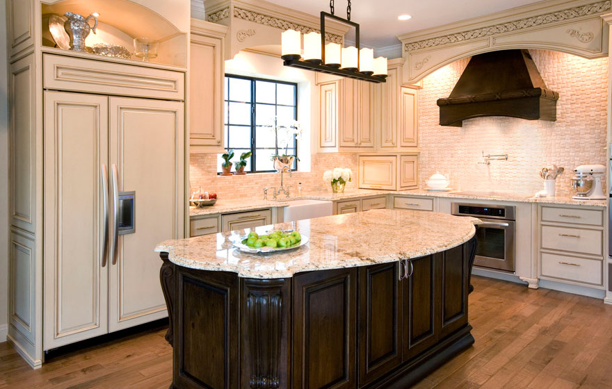 Dramatic and elegant, this two-tone kitchen design with light colored wall cabinetry keeps the space open and airy while the dark, luxurious island creates a rich focal point.
