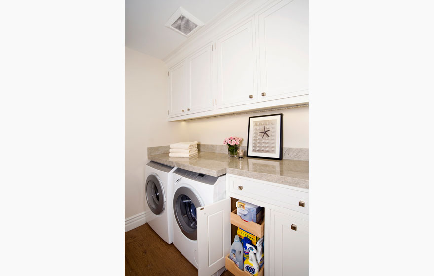 Custom designed wood cabinet doors in a compact laundry room off the kitchen for ease of use.